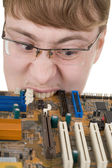 Guy bites an old circuit board — Stock Photo