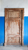 The closed old decayed door — Stock Photo