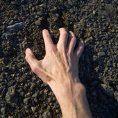 Hand clinging stony ground — Stock Photo