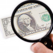 Counterfeit dollar on magnifier — Stock Photo