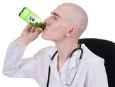 Man in doctor's smock with bottle — Stock Photo