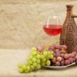 Royalty-Free Stock Photo: Ceramic brown bottle, grapes and goblet