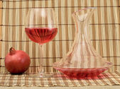 Glass of wine, decanter and pomegranate — Stock Photo