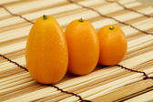 Fresh kumquat against a mat — Stock Photo