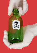 Green bottle with skull and crossbones — Stock Photo
