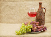 Ceramic brown bottle, grapes and goblet — Stock Photo
