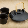 Black ceramic chinese teapot and mugs - Stock Photo