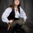 Girl - pirate with pistol sit on black — Stock Photo