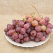 Grape on plate on textile background — Stock Photo