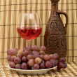 Carafe, grape and goblet on mat — 图库照片