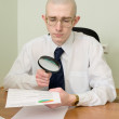 Stock Photo: Boss with magnifier on workplace
