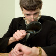 Person view a watch through a magnifier — Stock Photo #2269178