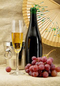 Champagne, bucket, goblet and grapes — Stock Photo