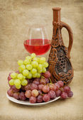 Ceramic bottle, grapes and red wine — Stock Photo