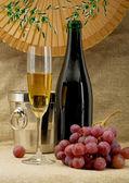 Garrafa de champanhe, balde, cálice e uvas — Fotografia Stock
