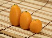 Three fresh kumquat against a mat — Stock Photo