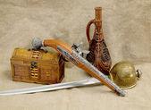 Bottle, rapier, sword, pistol and chest — Stock Photo