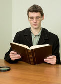 Guy in eyeglasses reads the book — Stok fotoğraf