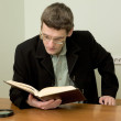 Guy in eyeglasses reads the book — Stock Photo