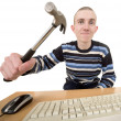 Young man with hammer and keyboard — Stock Photo