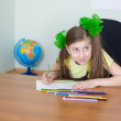 Girl sitting at a table with pencils - Stock Photo