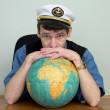 Man in uniform cap with globe — Stock Photo