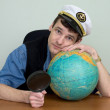 Man in uniform cap with globe — Stockfoto