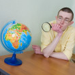 Young man with a magnifier and globe - Stock Photo