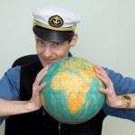 Man in a sea cap compresses globe — Stock Photo #2274632
