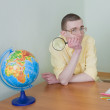 Stock Photo: Young mwith magnifier and globe