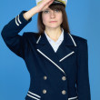 Girl in a sea uniform salutes - Stock fotografie