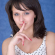Mysterious girl with a finger near lips — Stock Photo