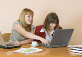 Girls work sitting at a table — Stock Photo