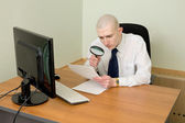 Businessman - a magnifier on a workplace — Stock fotografie