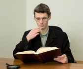 Guy in eyegasses reads the book — Stock Photo