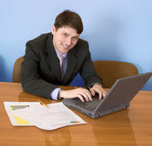 Businessman sits at table with laptop — Stock Photo