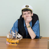 Man in a uniform cap at table with ship — Stock Photo