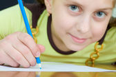 Girl holding a blue pencil — Stockfoto