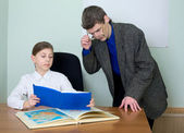 Tutor and schoolgirl with book and atlas — Stock Photo