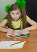 Girl drawing sitting at a table — Stockfoto
