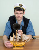Guy in a sea cap with toy sailing vessel — Stock Photo