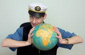 Man in a sea cap compresses globe — Stock Photo