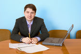 Businessman at a table with laptop — Stock Photo