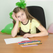 Stock Photo: Girl sitting at a table with pencils