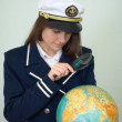 Royalty-Free Stock Photo: Girl - the captain examines the globe
