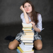 Girl sits having leant elbows on a books - Stock Photo