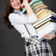 Schoolgirl bearing pile of books — Stock Photo #2286979