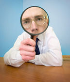 Man with a magnifier in a hand — Stock Photo
