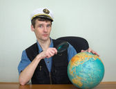 Guy in a sea uniform cap with globe — Stock Photo
