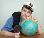 Man in a sea uniform cap with globe — Stock Photo